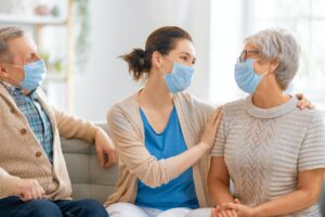 Adult daughter and senior parents wearing facemasks