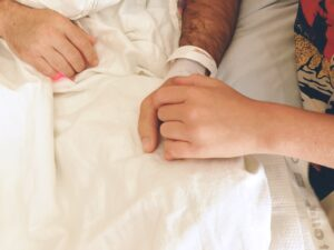 Child holding fathers hand in hospital.