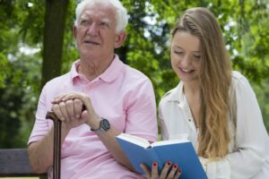 Woman reading to the elder man in the park