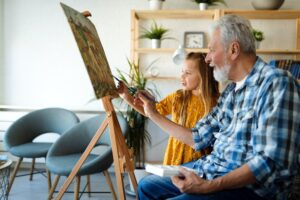 Portrait of senior man, grandfather teaching children painting. Happy family time