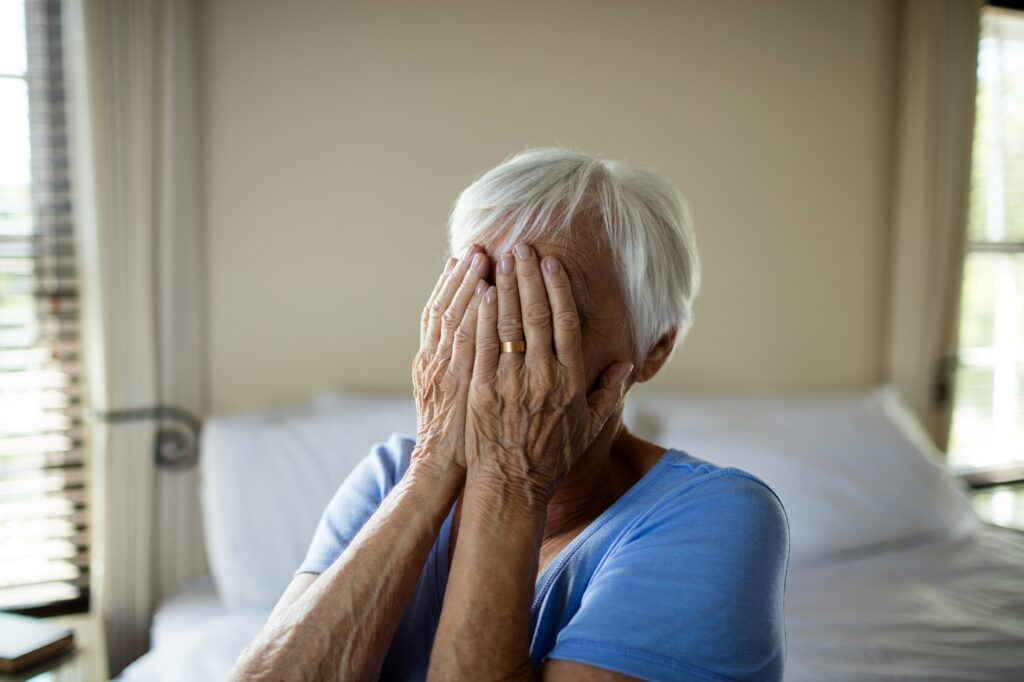 Stressed senior woman covering her face with hands